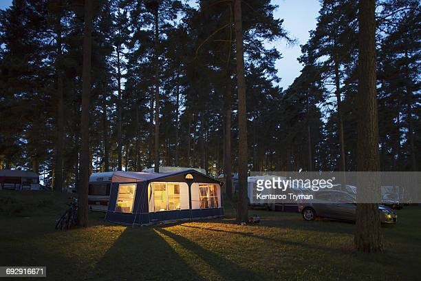 Caravans parked in travel trailer park by illuminated tent amidst trees at dusk