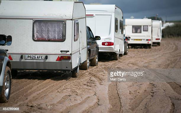 Caravans towed by cars drive through the mud as they arrive at the Great Dorset Steam Fair in Tarrant Hinton near Blandford on August 28 2014 in...
