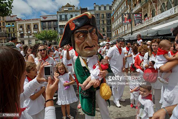 Caravinagre 'Vinegar face' kiliki holds a baby during the Comparsa de Gigantes y Cabezudos 'Giants and Big Heads parade' on the third day of the San...