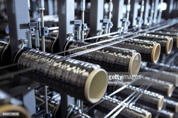Carbon fibre bobbins on loom in carbon fibre production facility