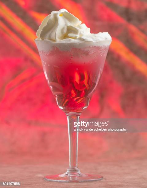 Carbonated water with grenadine and ice cubes and whipped cream on top..