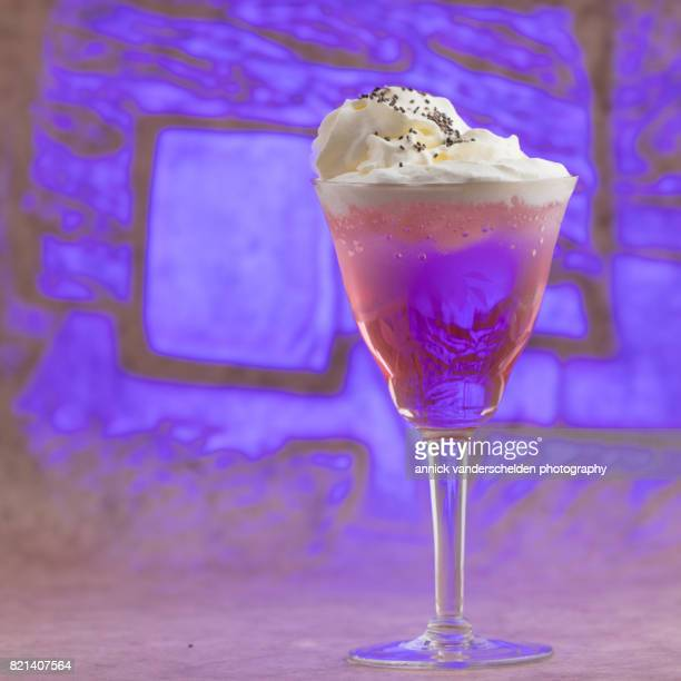 Carbonated water with grenadine and ice cubes and whipped cream with chia seeds on top..