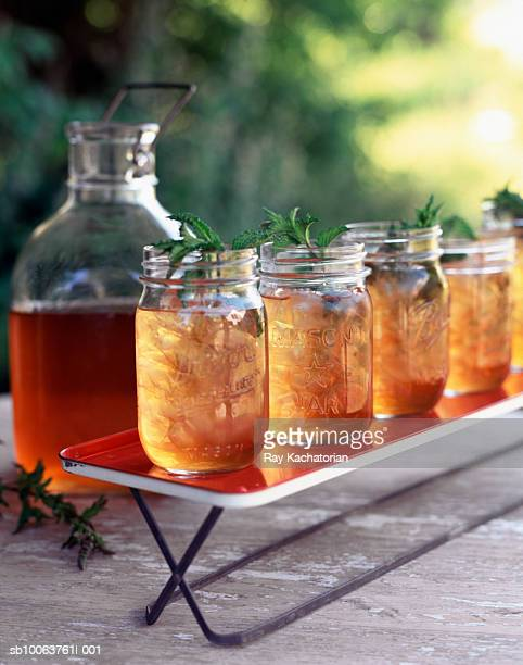 Carboy and jars of iced tea outdoors