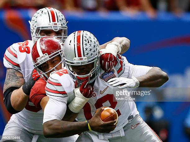 Cardale Jones of the Ohio State Buckeyes gest sacked by DJ Pettway of the Alabama Crimson Tide during the All State Sugar Bowl at the MercedesBenz...