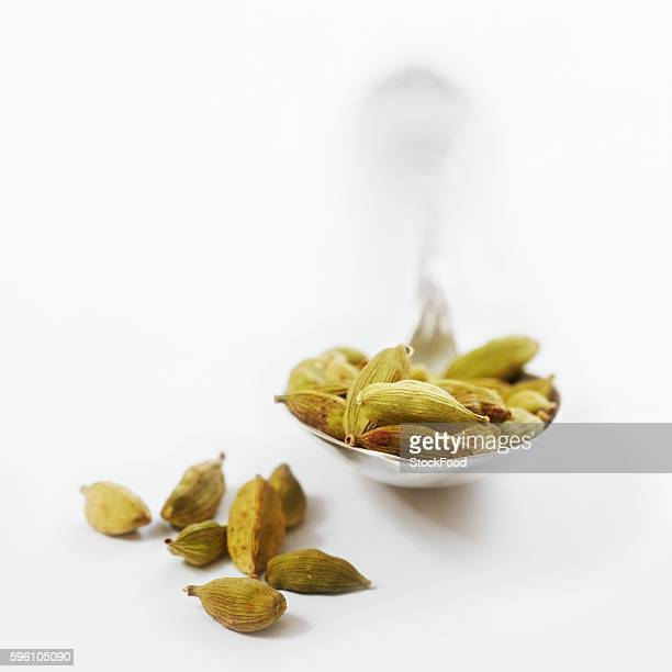cardamom pods, some on a spoon - cardamom stock photos and pictures