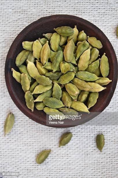 cardamom/spice in a clay bowl against white background - cardamom stock photos and pictures