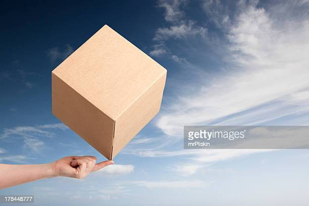 cardboard box balancing on fingertip - smooth stock photos and pictures
