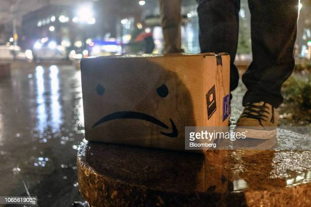 A cardboard box featuring an altered version of the Amazoncom Inc logo sits on the ground during a protest against the planned Amazon office hub in...