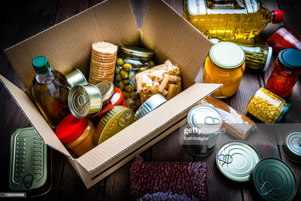 Cardboard box filled with non-perishable foods on wooden table. High angle view. : Stock Photo