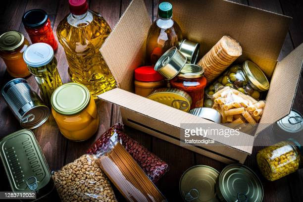 cardboard box filled with non-perishable foods on wooden table. high angle view. - box container stock pictures, royalty-free photos & images