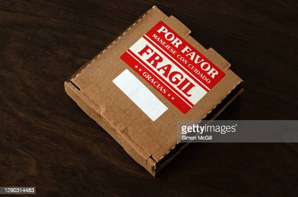 cardboard box parcel with a spanish-language fragile: handle with care label - fragile sticker stock pictures, royalty-free photos & images