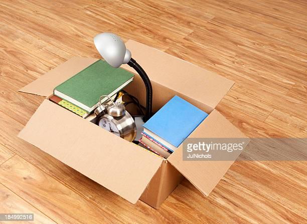 Caja de cartón con libros, lámpara de escritorio, y reloj despertador