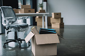cardboard box with folders and office supplies in floor during relocation