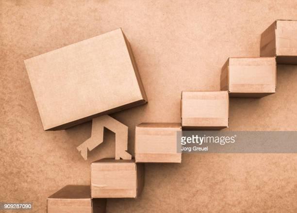 Cardboard box with legs climbing stairs