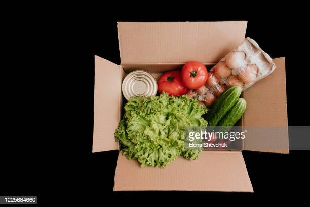 cardboard box with vegetables on a colored background.cucumbers, tomatoes, vegetable oil, eggs and canned goods isolated on black background.food supplies crisis food stock for quarantine.food delivery, donation, coronavirus.tape measure. - odessa crisis stock pictures, royalty-free photos & images