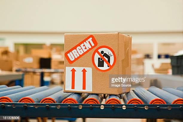 Cardboard box with warning stickers on conveyor belt