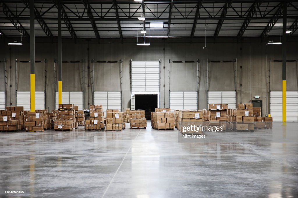 Cardboard boxes at loading dock in warehouse : Stock Photo