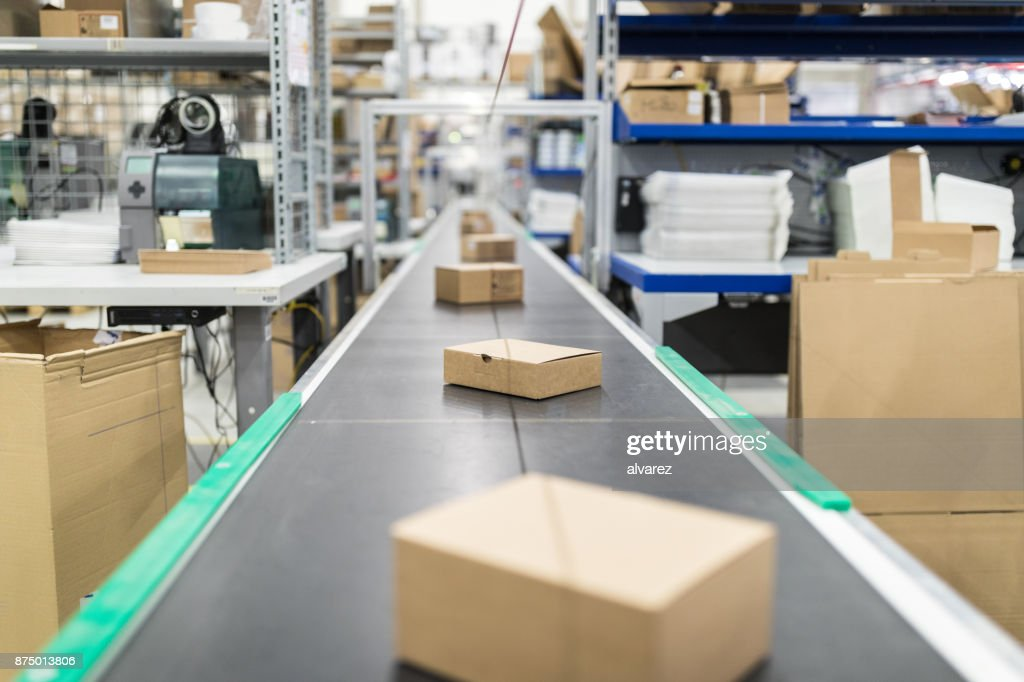 Cardboard boxes on conveyor belt at distribution warehouse : Stock Photo