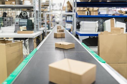Cardboard boxes on conveyor belt at distribution warehouse 875013806