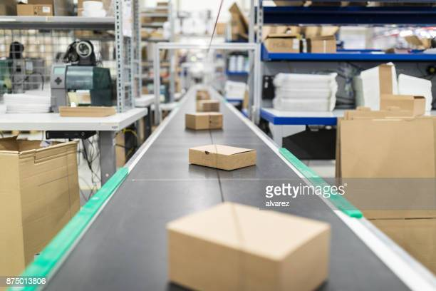 cardboard boxes on conveyor belt at distribution warehouse - mercanzia foto e immagini stock