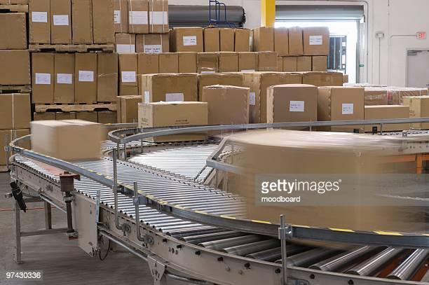 Cardboard boxes on conveyor belt in distribution warehouse