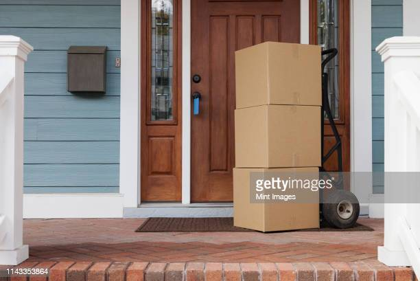 cardboard boxes on front porch of new house - ポーチ ストックフォトと画像