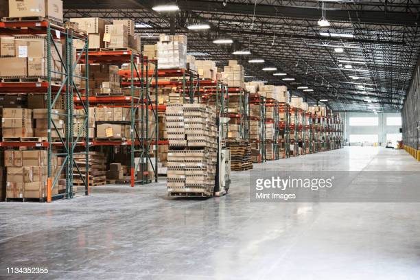 cardboard boxes on shelves in warehouse - construction material stock pictures, royalty-free photos & images