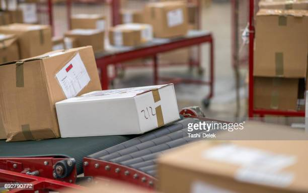 cardboard boxes package on conveyor belt - post structure stock photos and pictures
