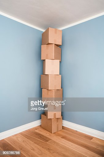 Cardboard boxes stacked in the corner of a room
