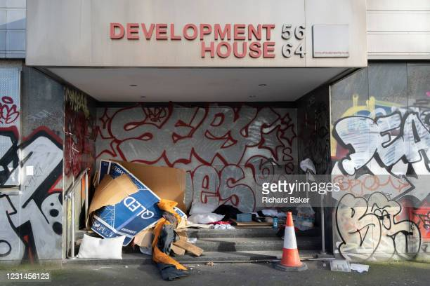 Cardboard boxes used for sheltering in and bedding to sleep under by homeless rough sleeper occupies the entrance of a former office property in...