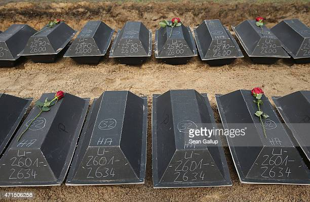 Cardboard coffins containing the remains of World War II German war dead about to be interred into a mass grave lie at a ceremony held by the German...