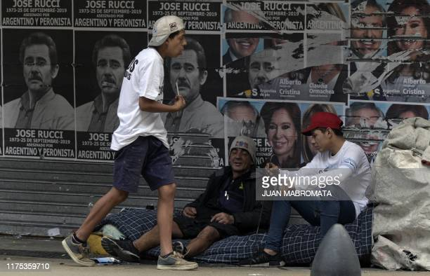 Cardboard collectors rest next posters depicting Peronist Jose Rucci killed in 1973 and demaged political propaganda of the Frente de Todos oposition...