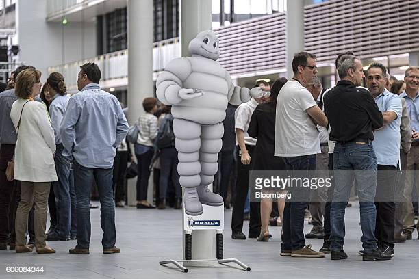 A cardboard cut out of the Michelin Cie Bibendum mascot also known as the Michelin Man stands as guests talk in the atrium of the new Michelin Cie...