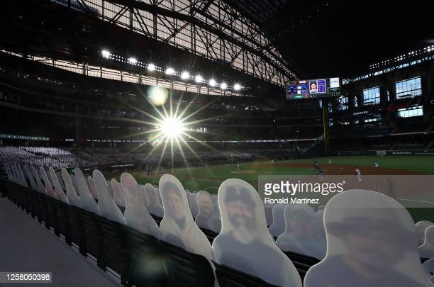 Cardboard cut-out images of fans are seen as the sun sets in the third inning of play between the Colorado Rockies and the Texas Rangers on Opening...