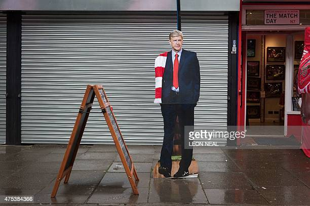A cardboard cutout of Arsenal manager Arsene Wenger stands outside a shop by the Emirates Stadium during the Arsenal victory parade in London on May...