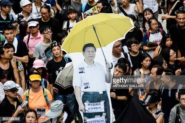 TOPSHOT A cardboard cutout of China's President Xi Jinping holding a yellow umbrella a symbol of the 2014 'Umbrella Movement' is carried during a...