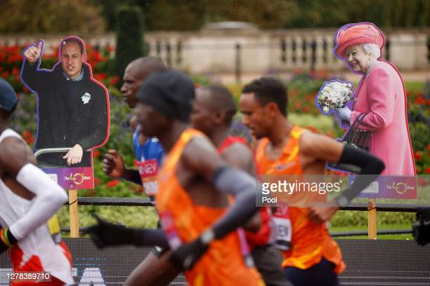 A cardboard cutout of Queen Elizabeth II is seen as runners compete in the Elite Men's race during the 2020 Virgin Money London Marathon around St...