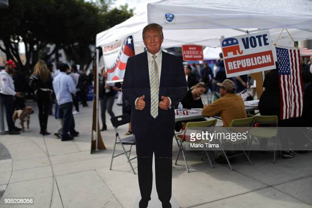 A cardboard cutout of US President Donald Trump stands at a Republican voter registration tent following a naturalization ceremony on March 20 2018...