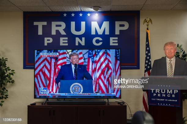 Cardboard cutout of US President Donald Trump stands next to the TV showing his acceptance speech for the Republican Party nomination for reelection...