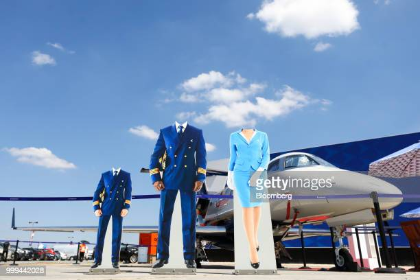 Cardboard cutouts of aircrew stand on display near the Embraer SA stand during preparations ahead of the Farnborough International Airshow 2018 in...