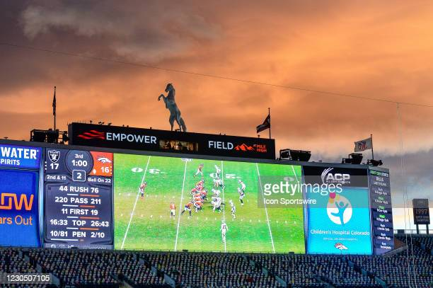 Cardboard cutouts of South Park cartoon characters are seen in the south stands of the stadium as the sun sets and the game is projected on the...