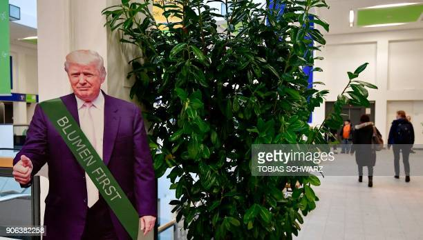 A cardboard depicting US President Donald Trump wearing a ribbon reading 'flowers first' is is installed in a hall before the opening day of the...