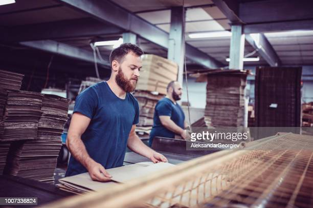 cardboard factory workers folding cartons and transporting pallets for shipping - carton stock pictures, royalty-free photos & images