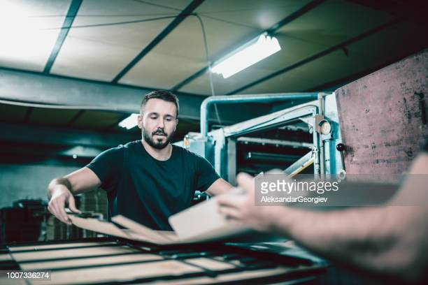 cardboard factory workers unfolding carton box and putting it on machine - printing press stock pictures, royalty-free photos & images