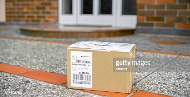 cardboard package at the doorstep during coronavirus pandemic - cardboard box stock pictures, royalty-free photos & images