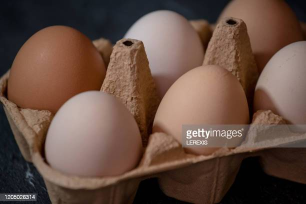cardboard package with eggs on a black background - lerexis stock pictures, royalty-free photos & images