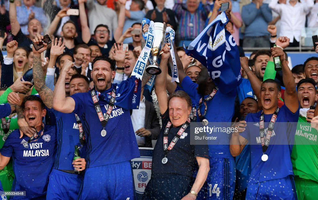 Cardiff captain Sean Morrison (l) and manager Neil Warnock celebrate promotion to the premier league with the squad after the Sky Bet Championship match between Cardiff City and Reading at Cardiff City Stadium on May 6, 2018 in Cardiff, Wales.
