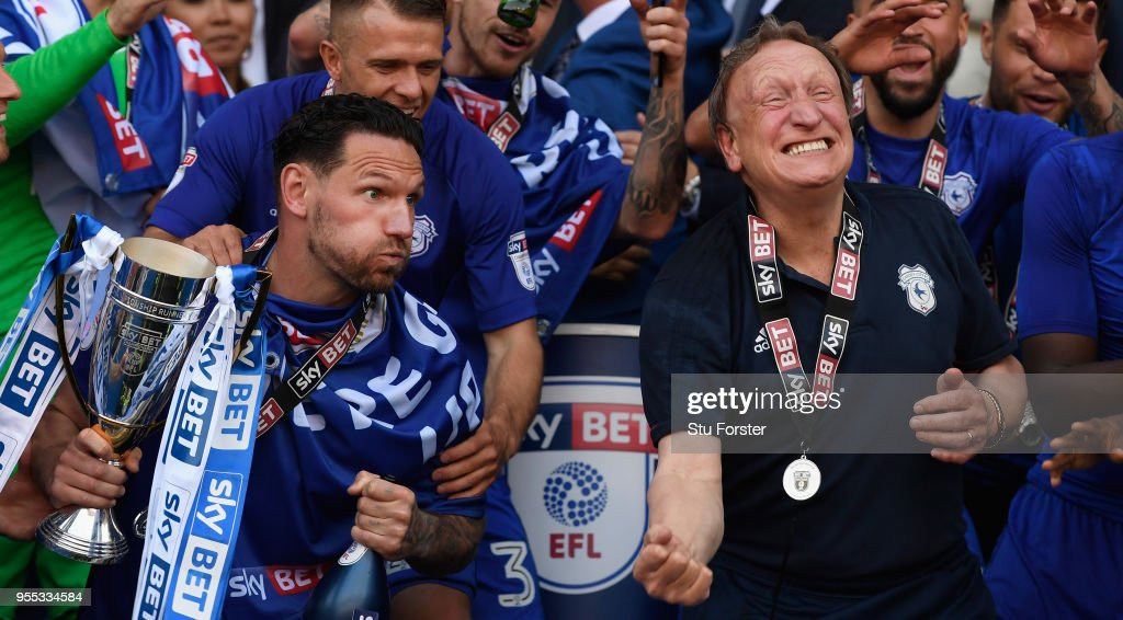Cardiff captain Sean Morrison (l) and manager Neil Warnock celebrate promotion to the premier league after the Sky Bet Championship match between Cardiff City and Reading at Cardiff City Stadium on May 6, 2018 in Cardiff, Wales.