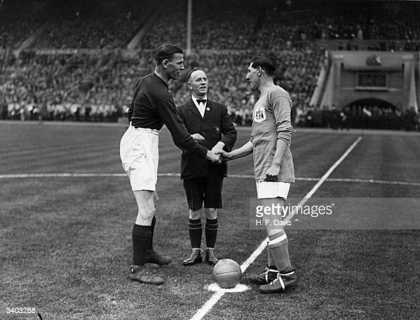 Cardiff City captain Fred Keenor shakes hands with the Arsenal captain before the kick off of the 1927 FA Cup final at Wembley stadium London Cardiff...