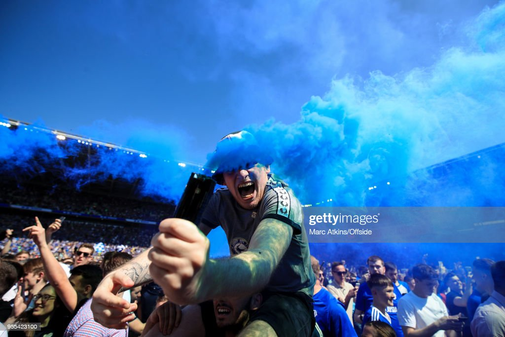 A Cardiff City fan celebrates promotion holding a smoke bomb during the Sky Bet Championship match between Cardiff City and Reading at Cardiff City Stadium on May 6, 2018 in Cardiff, Wales.